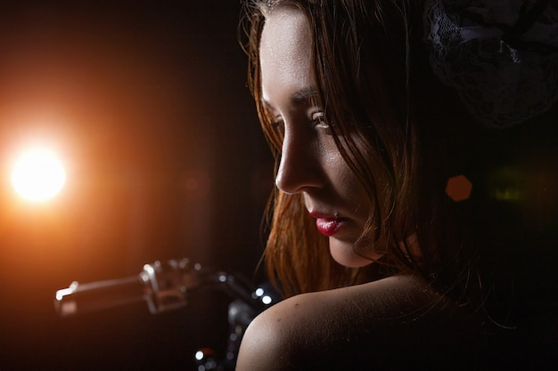 Портрет девушки, которая сидит на мотоцикле в темной комнате, светит фонарь Premium Фотографии