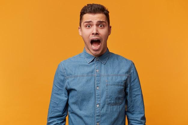 Портрет парня, который кричит в панике, кричит от страха, громко кричит, когда он поражен и очень напуган Бесплатные Фотографии