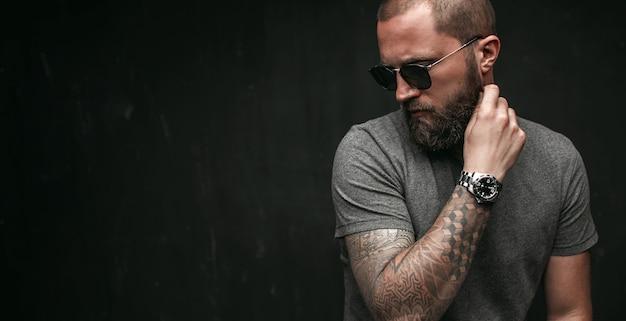 Портрет красивого лысого мужчины с длинной, хорошо подстриженной бородой, в темных очках и серой рубашке, отводящих взгляд в сторону Premium Фотографии