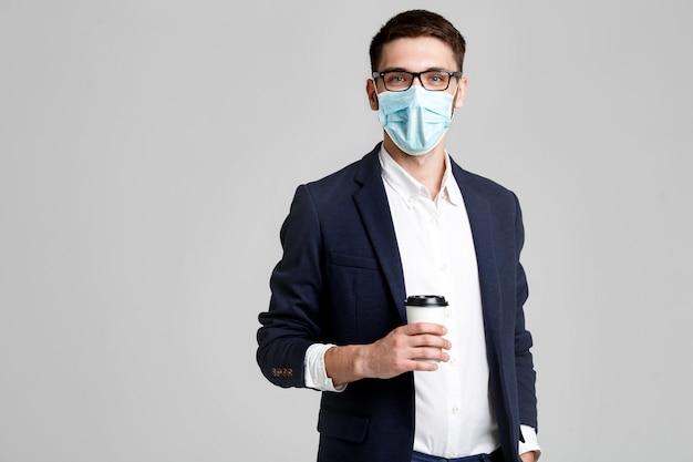 Портрет красивый бизнесмен в очки и маска для лица с чашкой кофе. Premium Фотографии
