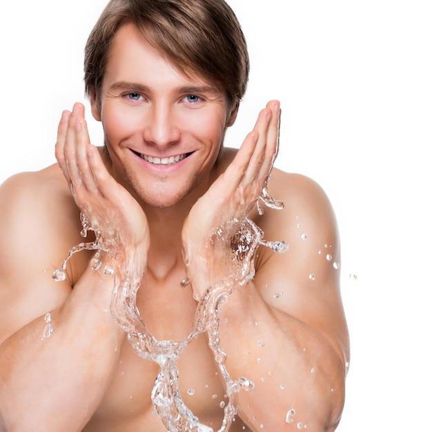 水で彼の健康な顔を洗うハンサムな笑顔の男の肖像画-白で隔離。 無料写真