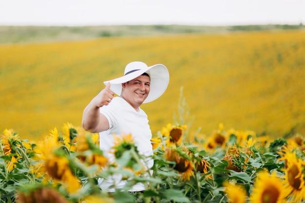 ひまわり畑で白人女性の帽子でハンサムな若い男の肖像画。男は屋外で楽しんでいます。コピースペース。セレクティブフォーカス Premium写真