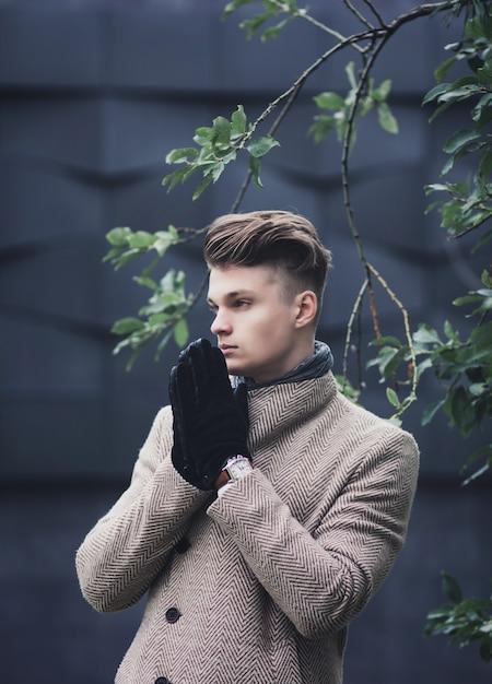 Портрет красивого молодого человека в перчатках, стоящего на городской улице Premium Фотографии