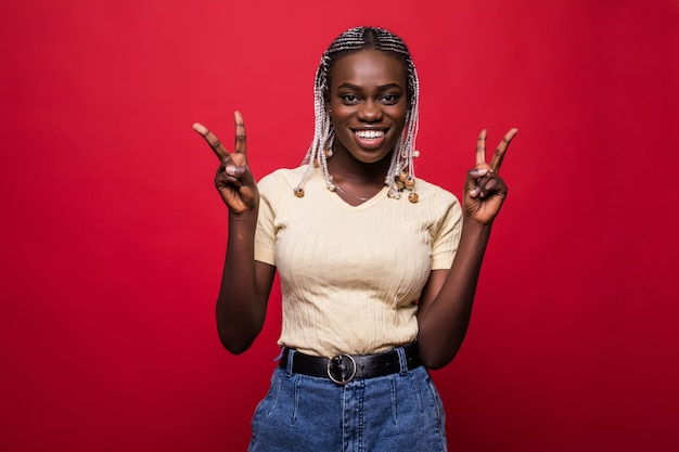 赤い背景の上の指で勝利を示す幸せなアフリカの女性の肖像画 Premium写真