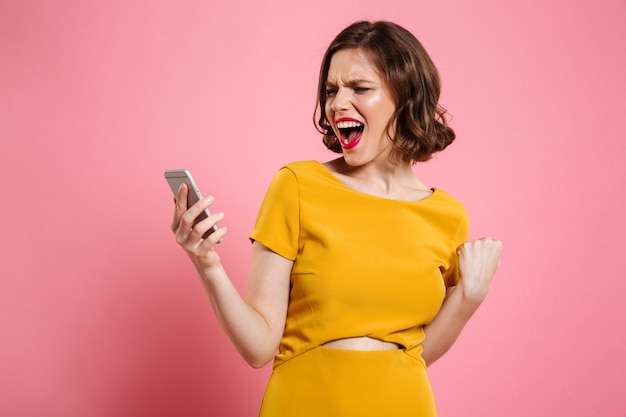 Портрет счастливой жизнерадостной женщины празднуя успех Бесплатные Фотографии