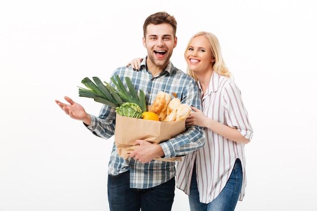 紙の買い物袋を保持している幸せなカップルの肖像画 無料写真