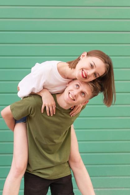 Портрет счастливой пары на бирюзе, молодой человек поднял девушку на спину Premium Фотографии