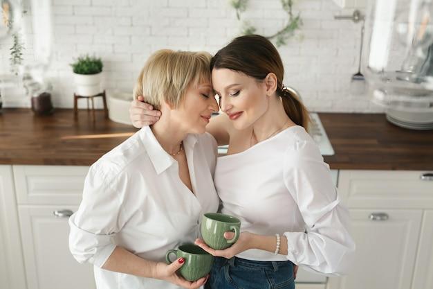 台所で幸せな高齢の母と娘の肖像、彼らはお茶を飲み、会話を楽しみます。自宅で大人の娘を持つ老母の優しい肖像画 Premium写真