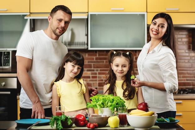 幸せな家族、ママのお父さんと2人の娘、自宅のキッチンでサラダを調理の肖像画。健康的な食事のコンセプト Premium写真