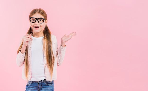 ピンクの背景に対して肩をすくめて眼鏡支柱を持って幸せな少女の肖像画 無料写真