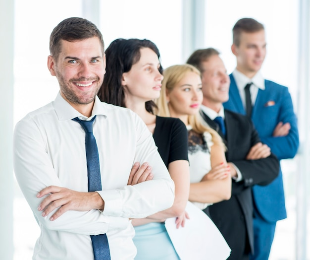 Portrait of a happy manager with his employees standing in a row Free Photo