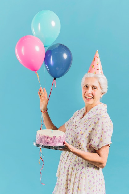 Portrait Of A Happy Woman With Birthday Cake And Balloons On Blue Backdrop Free Photo