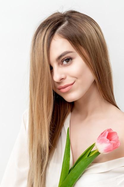 Портрет счастливой молодой кавказской женщины с одним розовым тюльпаном на белом фоне с копией пространства Premium Фотографии