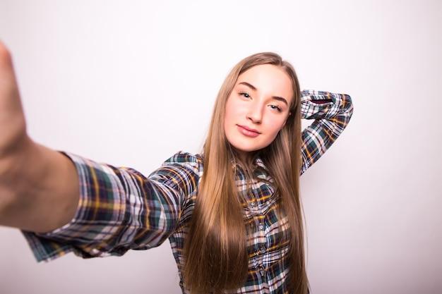 Портрет счастливой молодой девушки, делая смешное лицо, фотографируя себя изолированной над белой стеной Бесплатные Фотографии