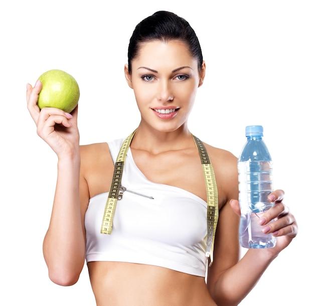 Портрет здоровой женщины с яблоком и бутылкой воды. здоровый фитнес и концепция образа жизни еды. Бесплатные Фотографии
