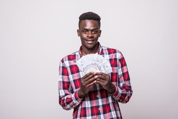 お金の紙幣を押しながら分離された見てうれしそうな興奮したアフロアメリカ人の肖像画 無料写真