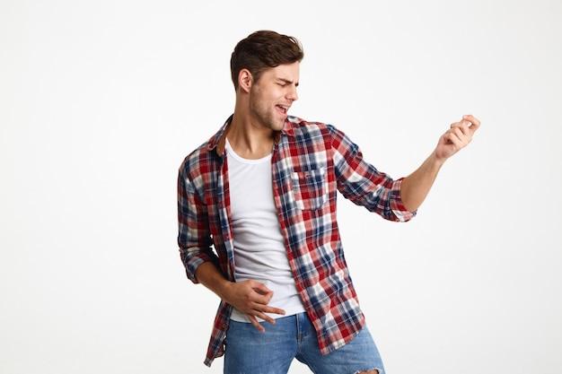 Портрет радостного молодого человека, играющего на гитаре Бесплатные Фотографии