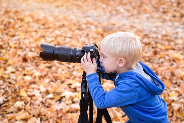 Портрет маленькой белокурой камеры на штативе Premium Фотографии