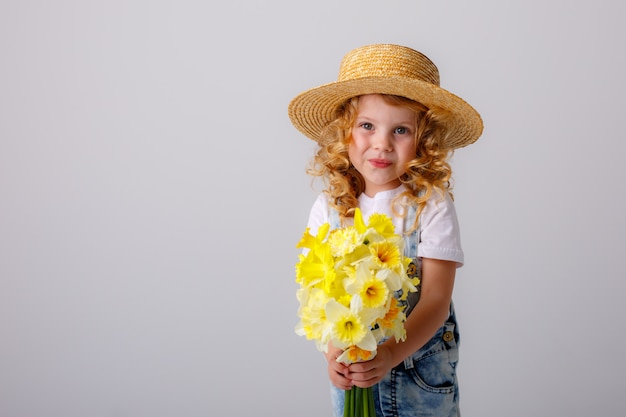 ホワイトスペースに麦わら帽子の春の花の花束を保持している金髪少女の肖像画 Premium写真