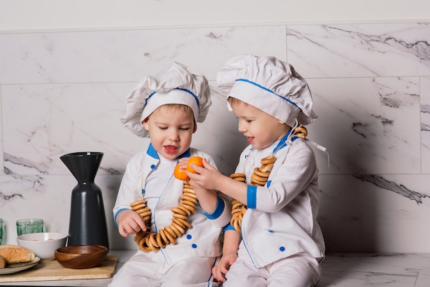 부엌에서 냄비를 들고 어린 소년 쿡의 초상화. 다른 직업. 흰색 배경 위에 격리. 쌍둥이 형제 프리미엄 사진