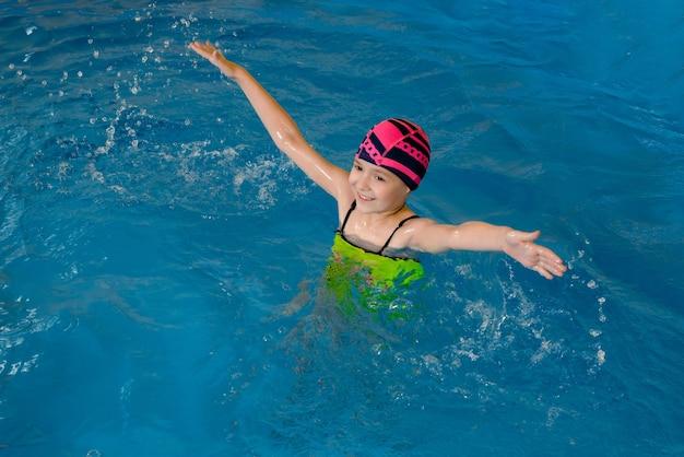 Портрет маленькой девочки с удовольствием в крытом бассейне Premium Фотографии