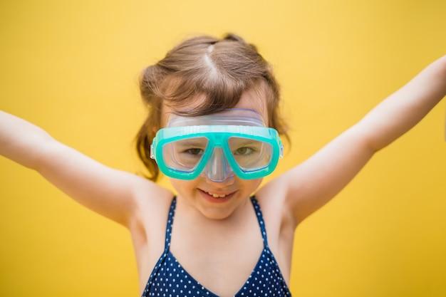 Портрет маленькой девочки в плавательных очках на желтом фоне изолированные с пространством для текста Premium Фотографии