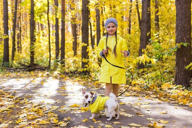 주황색과 노란색의 배경에 어린 소녀의 초상화는 단풍 화창한 날에 나뭇잎 프리미엄 사진