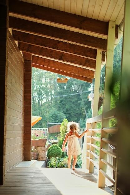 ベランダに沿って外を歩く少女の肖像画、 Premium写真