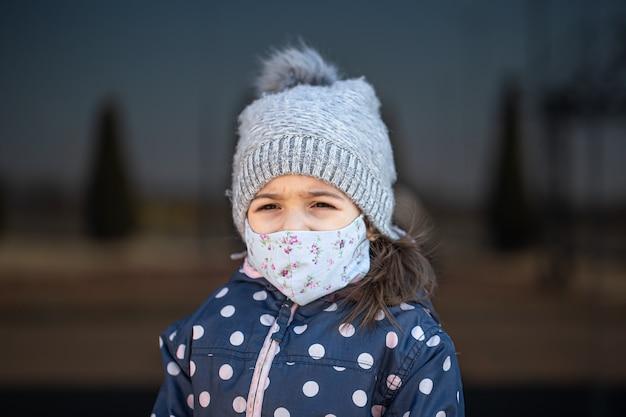 コロナウイルスのパンデミック時に帽子とマスクをかぶった少女の肖像画。 無料写真