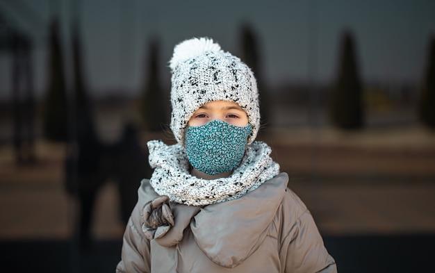 コロナウイルスのパンデミック時に帽子とマスクをかぶった少女の肖像画。 Premium写真