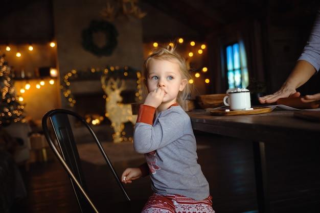 Портрет маленькой девочки, которая ест зефир, а ее бабушка готовит традиционное печенье. концепция уютного рождества. Premium Фотографии