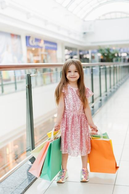 쇼핑몰에서 작은 행복 한 여자의 초상화. 그녀의 손에 멀티 가방 핑크 드레스에 웃는 웃는 소녀 쇼핑에 종사하고있다. 광고 템플릿 프리미엄 사진
