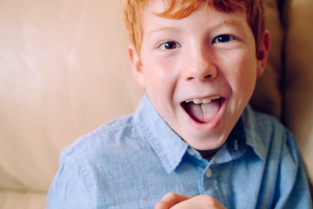 Портрет маленького рыжего мальчика, открыв рот с выражением удивления. Premium Фотографии
