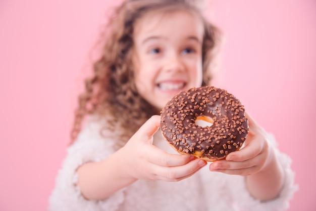 ドーナツと少し微笑んでいる女の子の肖像画 無料写真