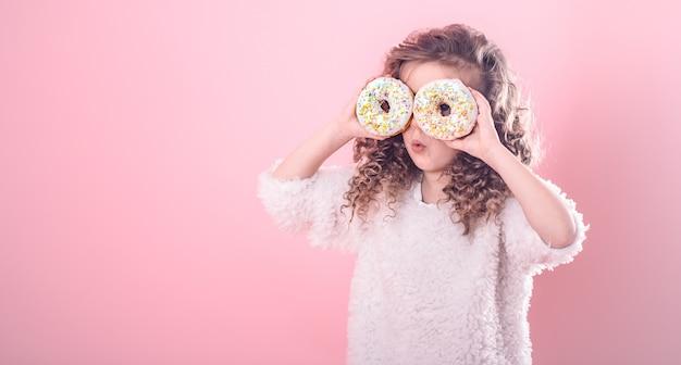 ドーナツと少し驚いた少女の肖像画 無料写真