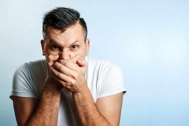 Портрет мужчины, прикрывает рот руками, цензура, свобода слова. понятие языка тела, эмоций человека, реакции. Premium Фотографии