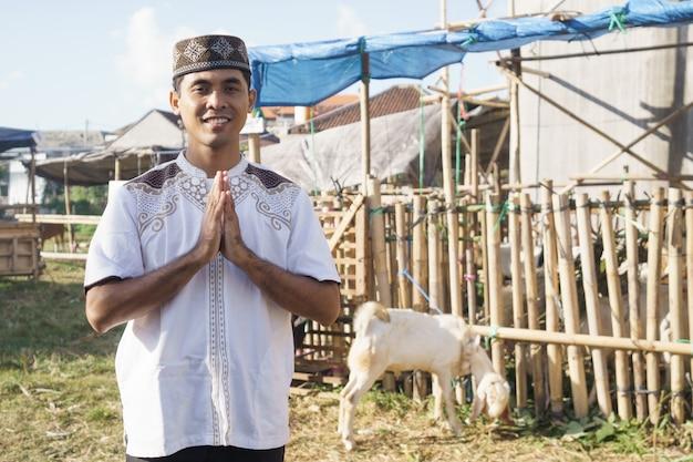 Портрет мужчины-мусульманина, стоящего перед козьей фермой. концепция жертвоприношения ид адха Premium Фотографии