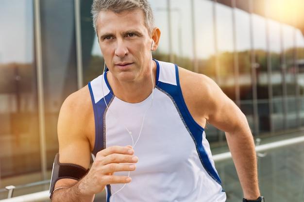 イヤホンでジョギング中年の男性アスリートの肖像 Premium写真