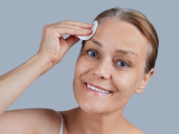 コットンパッドを使用して裸の肩を持つ成熟した女性の肖像画。フェイシャルスキンケアのコンセプト。 Premium写真