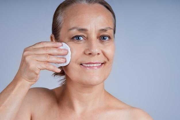 コットンパッドを使用して裸の肩を持つ成熟した女性の肖像画。 Premium写真