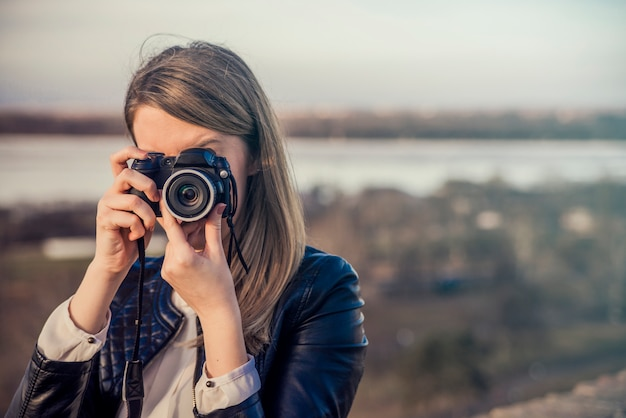 Portrait of a photographer covering her face with the camera. Ph Free Photo