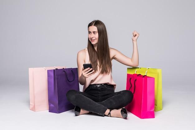 買い物袋が付いている床に座って、灰色の壁を越えて勝利ジェスチャーで携帯電話を使用してかなり若い女性の肖像画 無料写真