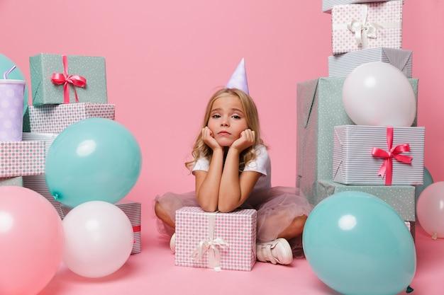 생일 모자에 슬픈 어린 소녀의 초상화 무료 사진