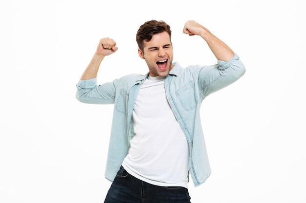 Портрет удовлетворенного молодого человека, празднующего успех Бесплатные Фотографии