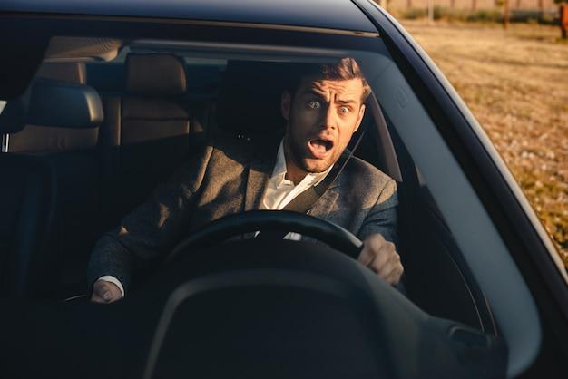 車をほぼクラッシュする叫んでいるビジネスマンの肖像画 Premium写真