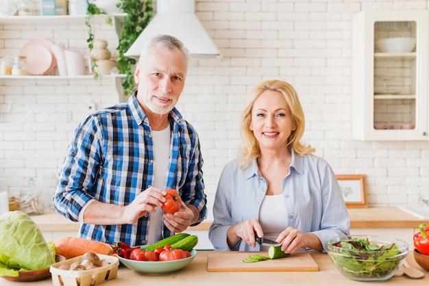 モダンなキッチンでカメラを見て食べ物を準備する年配のカップルの肖像画 無料写真