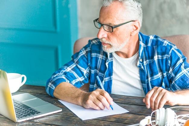 Портрет старшего человека, писать заметки, используя ноутбук на столе Бесплатные Фотографии