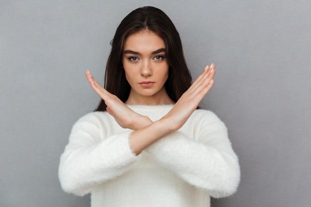 交差させた手ジェスチャーを示す深刻な若い女性の肖像画 無料写真