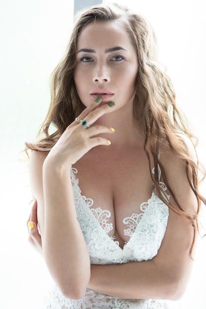 그녀의 입술에 그녀의 손을 만진 레이스 속옷에 섹시한 젊은 여자의 초상화 프리미엄 사진