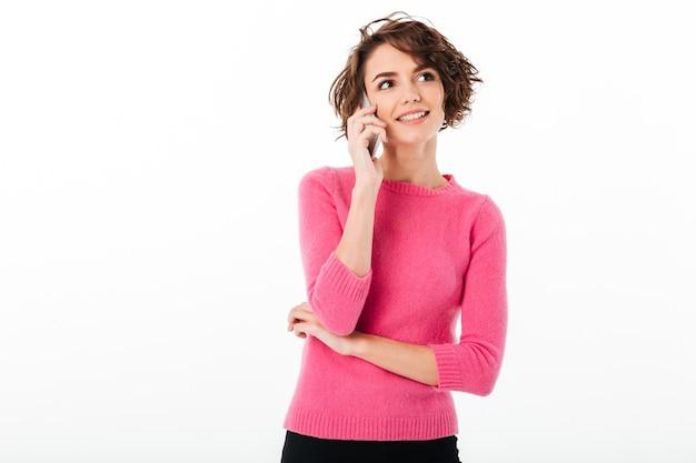 Портрет улыбающегося привлекательная девушка разговаривает по мобильному телефону Бесплатные Фотографии